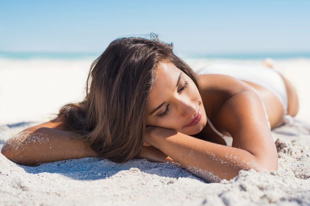Beautiful woman lying on sand