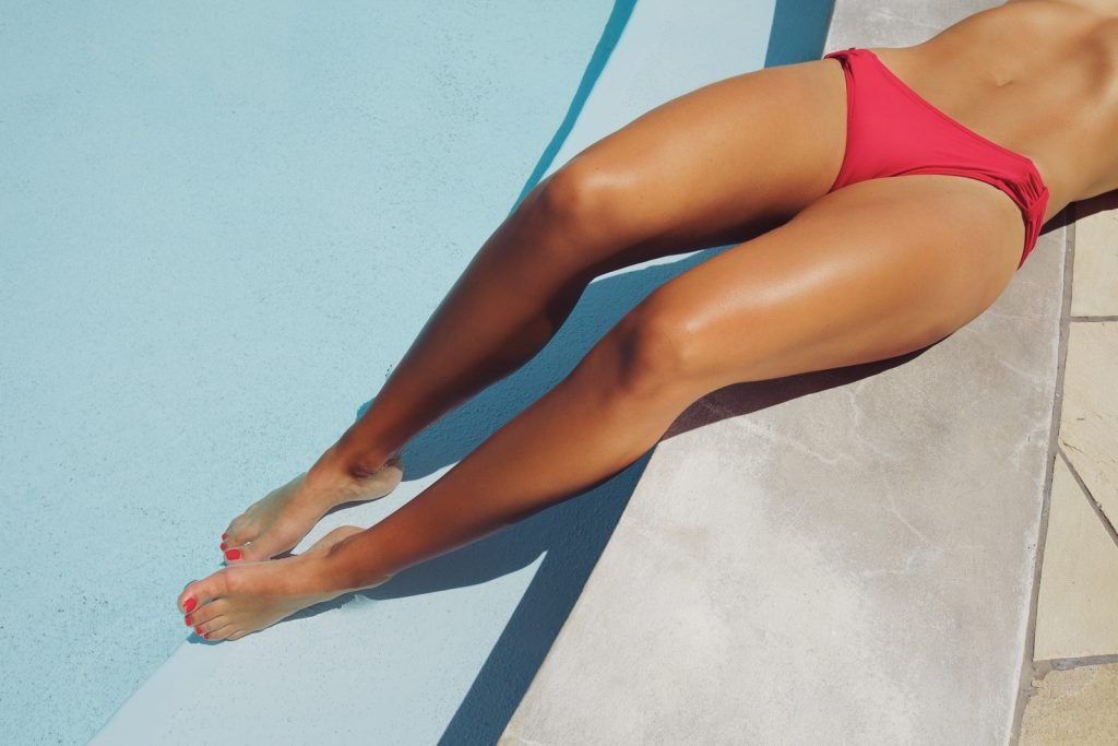 Pretty young woman resting by the poolside