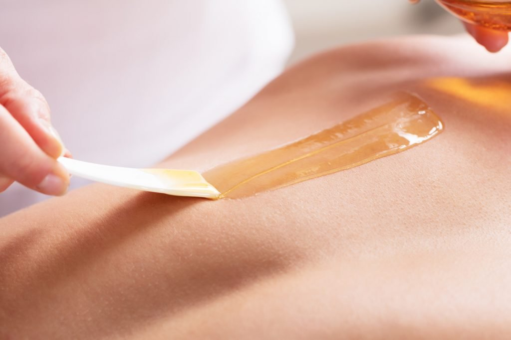 Woman Waxing Man's Chest With Wax Strip
